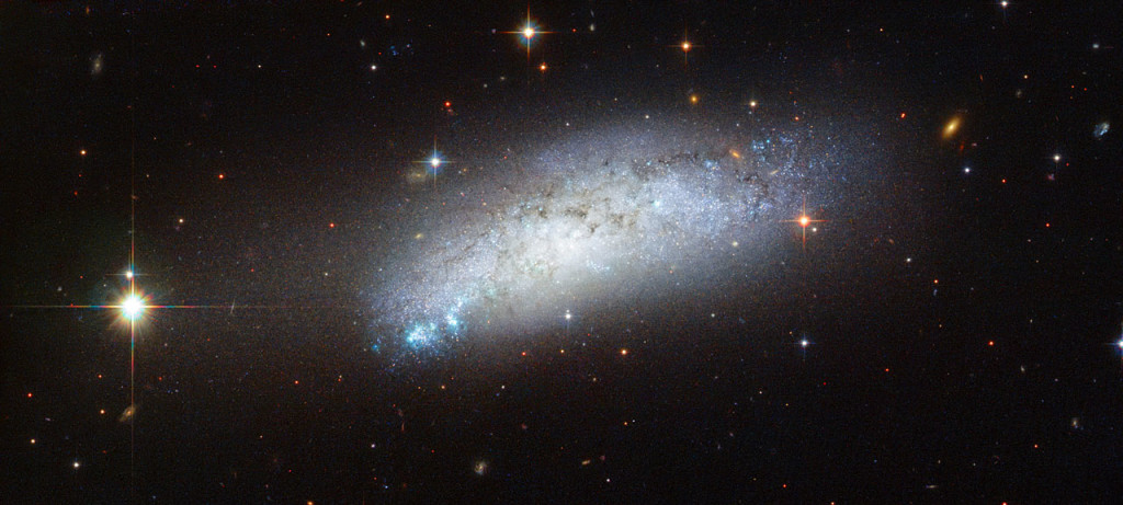 This galaxy goes by the name of ESO 162-17 and is located about 40 million light-years away in the constellation of Carina. At first glance this image seems like a fairly standard picture of a galaxy with dark patches of dust and bright patches of young, blue stars. However, a closer look reveals several peculiar features. Firstly, ESO 162-17 is what is known as a peculiar galaxy — a galaxy that has gone through interactions with its cosmic neighbours, resulting in an unusual amount of dust and gas, an irregular shape, or a strange composition. Secondly, on 23 February 2010 astronomers observed the supernova known as SN 2010ae nestled within this galaxy. The supernova belongs to a recently discovered class of supernovae called Type Iax supernovae. This class of objects is related to the better known Type-Ia supernovae. Type Ia supernovae result when a white dwarf accumulates enough mass either from a companion or, rarely, through collision with another white dwarf, to initiate a catastrophic collapse followed by a spectacular explosion as a supernova.  Type Iax supernovae also involve a white dwarf as the central star, but in this case it may survive the event. Type Iax supernovae are much fainter and rarer than Type Ia supernovae, and their exact mechanism is still a matter of open debate. The rather beautiful four-pointed shape of foreground stars distributed around ESO 162-17 also draws the eye. This is an optical effect introduced as the incoming light is diffracted by the four struts that support the Hubble Space Telescope's small secondary mirror.